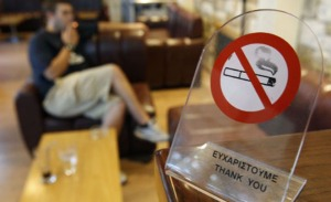 A man smokes a cigarette behind a smoking ban sign in a cafe in Chalandri suburb, north of Athens