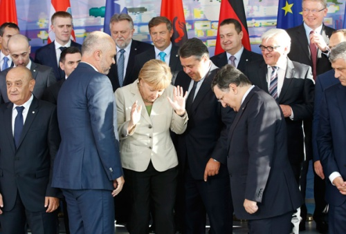 """German Chancellor Merkel reacts as she poses for a group picture at the """"West Balkan Conference"""" in Berlin"""