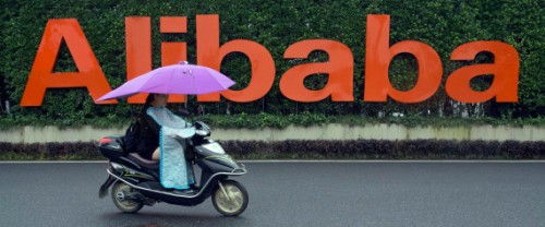 A woman rides a bike past the company logo outside the Alibaba Group headquarters in Hangzhou, in eastern China's Zhejiang province on Friday, May 27, 2016.  Alibaba began 17 years ago in the modest living room of a gutsy man with a history of failure. Jack Ma struggled in school, and even Kentucky Fried Chicken refused to hire him. Today, Alibaba is a $15.7 billion e-commerce ecosystem that supports the livelihoods of tens of millions of merchants. Some 423 million shoppers last fiscal year picked through the billion listings that Alibaba's platforms host on any given day. (AP Photo/Ng Han Guan)